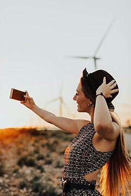 Young woman taking selfie at sunset - p300m2023747 by Oriol Castelló Arroyo