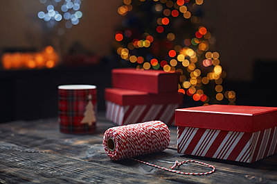 Roll of red-white packthread and gift boxes in front of lighted Christmas tree - p300m2023827 by Arman Zhenikeyev