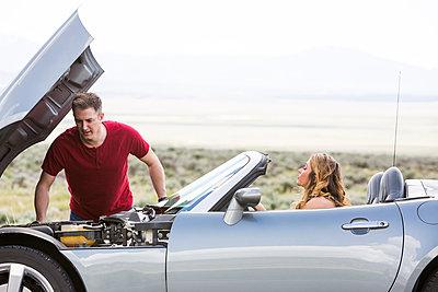 Caucasian man examining car engine at vehicle breakdown - p555m1304988 by Mike Kemp