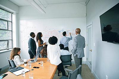 Businessman writing on whiteboard in meeting - p555m1504099 by John Fedele