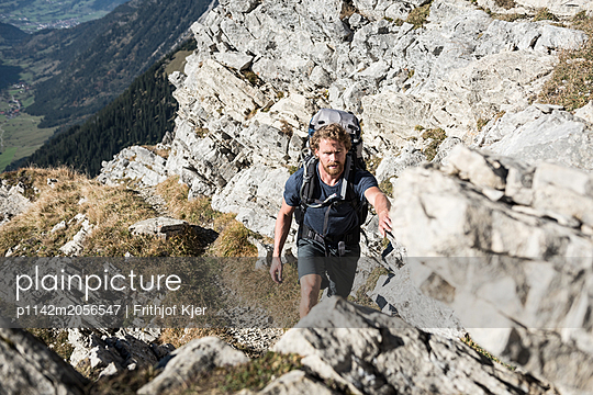 Junger Mann wandert auf steinigem Weg  - p1142m2056547 von Runar Lind