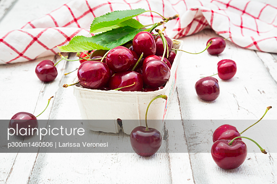 Cardboard box of cherries, leaves and kitchen towel on white wood