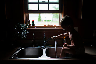 Playful boy washing legs while sitting at kitchen sink - p1166m1176227 by Cavan Images