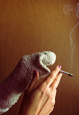 sock puppet smoking a cigarette. - p1166m2171713 by Cavan Images