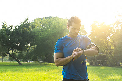 Runner in urban park checking his smartwatch - p300m1549656 by Steve Brookland