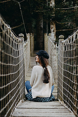 Smiling young woman sitting on a suspension bridge - p300m1549797 by Oriol Castelló Arroyo