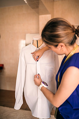 Young female dressmaker adjusting shirt on mannequin - p300m2293534 by LUPE RODRIGUEZ