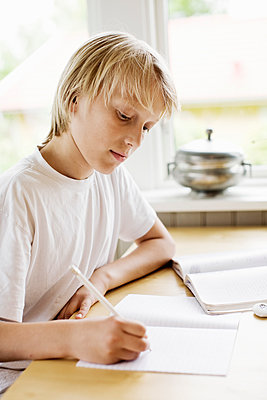 Boy writing in book on table at home - p426m1148028 by Kentaroo Tryman