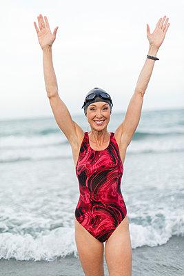Caucasian swimmer standing on beach - p555m1410757 by Rick Gomez