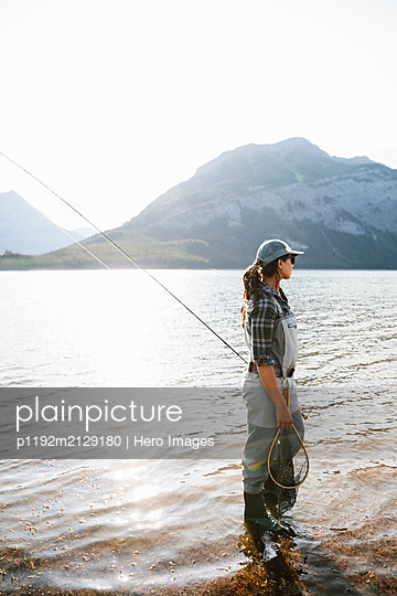 Woman fly fishing in sunny lake - p1192m2129180 by Hero Images