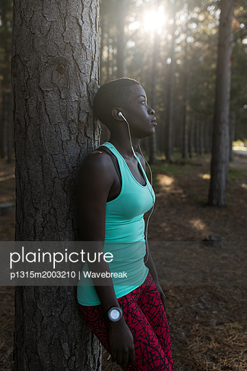 Exhausted female athlete leaning against the tree trunk in the forest - p1315m2003210 by Wavebreak