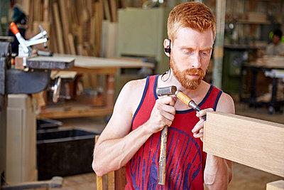 Craftsperson wearing earphones while working in workshop - p1166m1489744 by Cavan Images