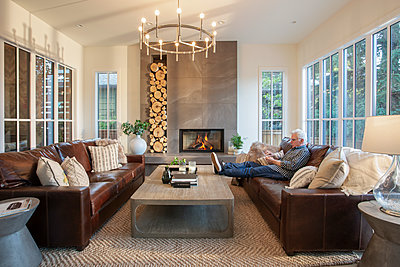Senior man relaxing on living room sofa next to fireplace - p1192m2047667 by Hero Images