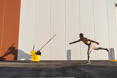 Acrobat playing with cleaning bucket and mop - p300m2012391 von VITTA GALLERY
