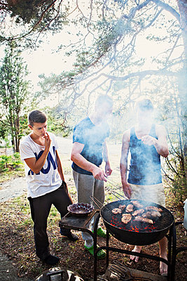 Father with two sons having barbecue - p312m970028f by Lieselotte Van Der Meijs