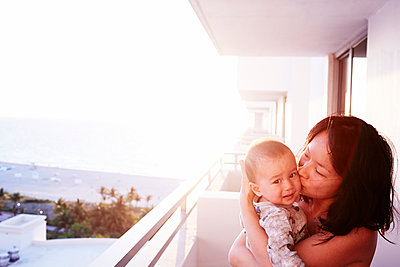 Portrait of mid adult mother and baby son on apartment balcony - p429m958260 by JPM
