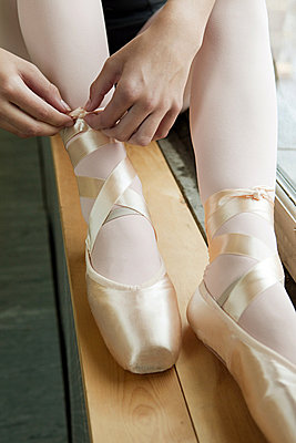Girl tying ballet shoes - p9245549f by Image Source