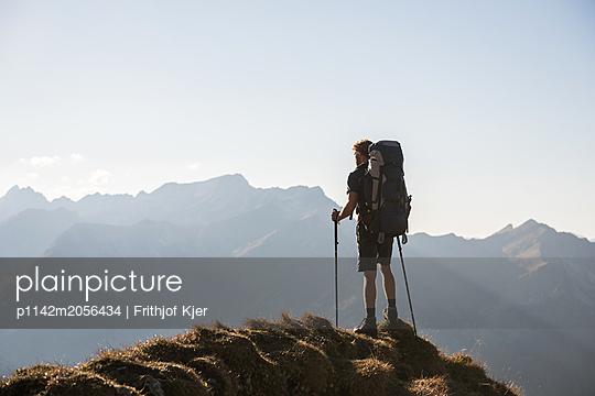 Junger Wanderer genießt Ausblick in den Bergen  - p1142m2056434 von Runar Lind