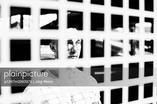 Man looking out of grilled window - p1267m2263376 by Jörg Meier
