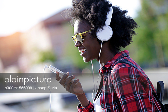 Portrait of laughing young woman using headphones and cell phone - p300m1586999 von Josep Suria