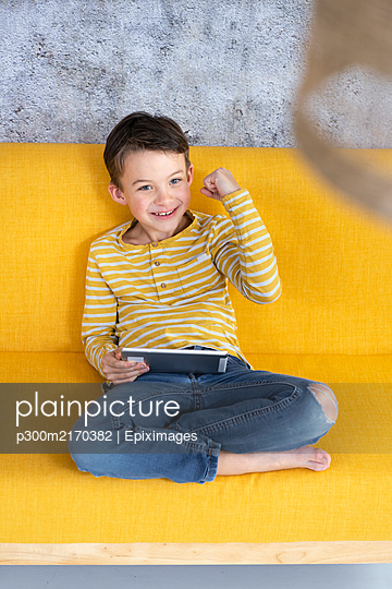 Boy playing with tablet on yellow couch - p300m2170382 by Epiximages