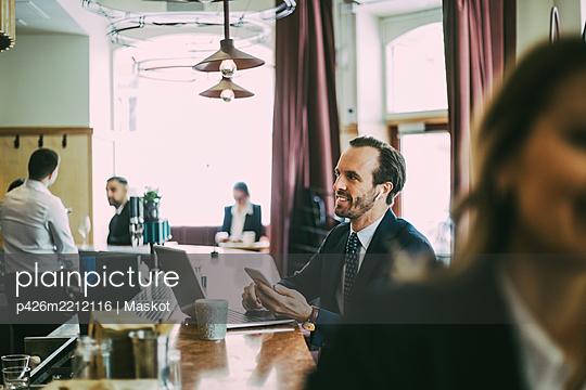 Smiling male entrepreneur using phone in restaurant - p426m2212116 by Maskot