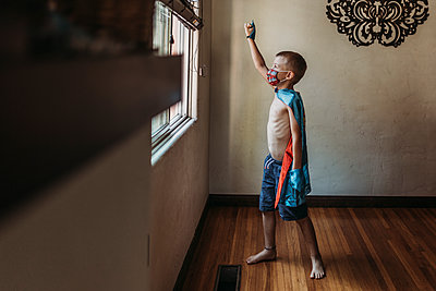 Young boy dressed as super hero with mask standing by window at home - p1166m2207777 by Cavan Images