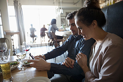 Young couple with smart phone at bar table - p1192m1567188 by Hero Images