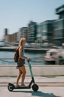 Junge Frau unterwegs mit dem E-Scooter - p299m2108622 von Silke Heyer