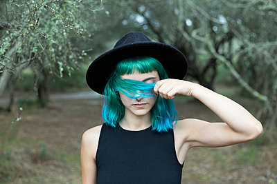Portrait of young woman with dyed blue and green hair wearing black hat on rainy day - p300m2120831 by Sus Pons