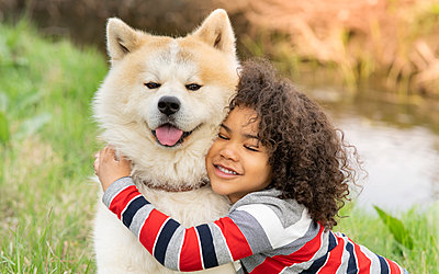Smiling boy embracing dog in nature - p300m2265893 by Jose Carlos Ichiro