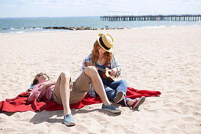 Couple sunbathing and playing ukulele on beach - p924m937034f by Steve Prezant