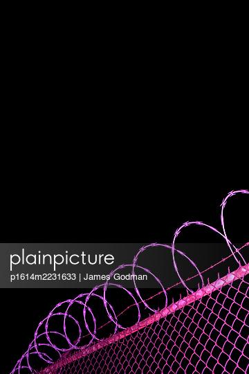 Razor wire fence at night - p1614m2231633 by James Godman