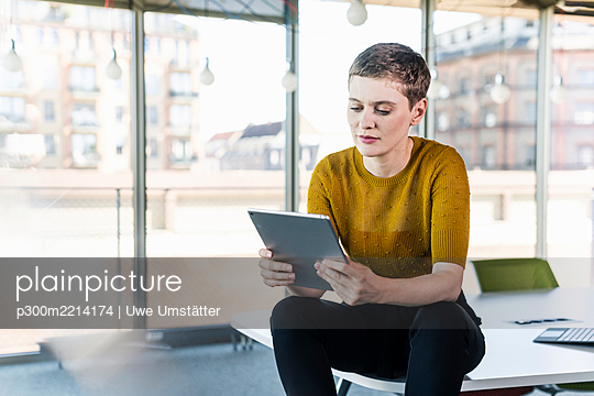 Businesswoman sitting on desk in office using tablet - p300m2214174 by Uwe Umstätter