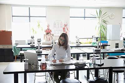 Girl middle school student conducting scientific experiment in science laboratory - p1192m1473259 by Hero Images