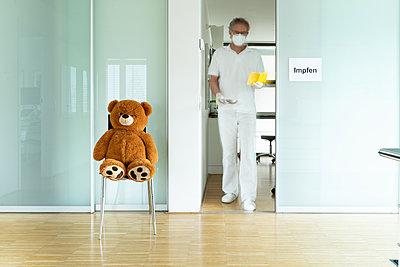 Arzt mit Mundschutz und Teddybär in einer Arztpraxis, Corona-Impfung - p1625m2254144 von Dr. med.