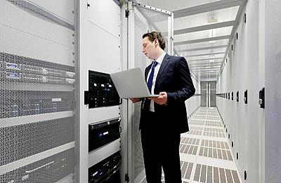 Businessman using laptop in server room - p429m665481f by Mischa Keijser