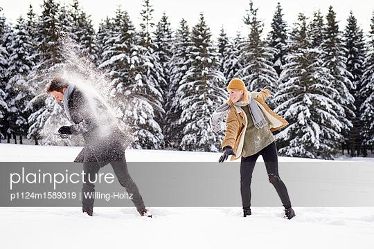 Junges Paar macht eine Schneeballschlacht - p1124m1589319 von Willing-Holtz