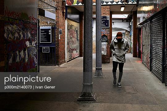 Man walking in an underpass, London, UK - p300m2140073 by Ivan Gener
