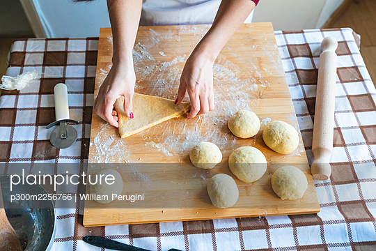 Woman making dough balls on cutting board to make croissants in kitchen - p300m2256766 by William Perugini