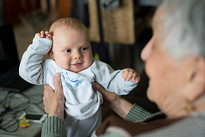 Portrait of baby boy being held by his great-grandmother - p300m1058979f by Ramon Espelt