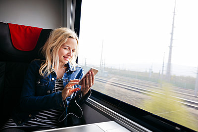 Smiling blond woman travelling by train using smartphone and earphones - p300m2103560 von Epiximages