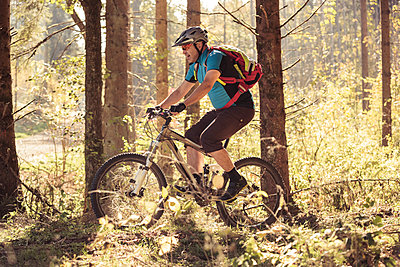 Man riding mountainbike on forest track - p300m2104358 by Sebastian Dorn