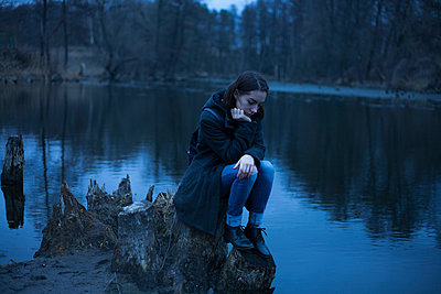 Caucasian woman sitting on tree stump near river thinking - p555m1522916 by Dmitriy Bilous