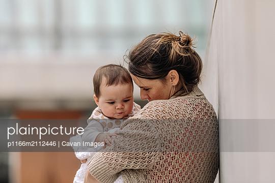 Side view of mother hugging her baby outdoor - p1166m2112446 by Cavan Images
