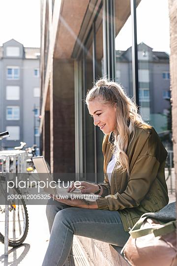 Friends sitting in front of window in the city, using laptop - p300m2005325 von Uwe Umstätter