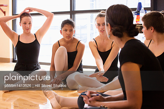 Ballet dancers listening to teacher in studio