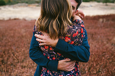 Couple kissing while standing on grassy field - p1166m1210230 by Cavan Images