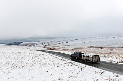 A four wheel drive vehicle and trailer with sheep negotiates a road through a wintry landscape in the Elan Valley area in Powys, Wales, United Kingdom, Europe - p871m1136152 by Graham Lawrence