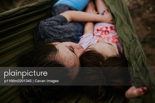 Girls laying in hammock snuggling together - p1166m2201345 by Cavan Images